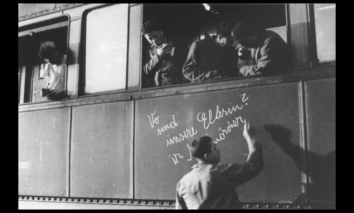 "A young survivor writes, ""where are our parents?' on the side of a train from Buchenwald to France"
