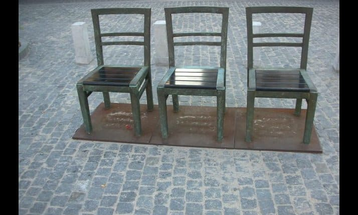 Memorial to victims of the Krakow ghetto in the form of oversized bronze chairs on the Plac Bohaterow Getta. (See below for detailed explanation)