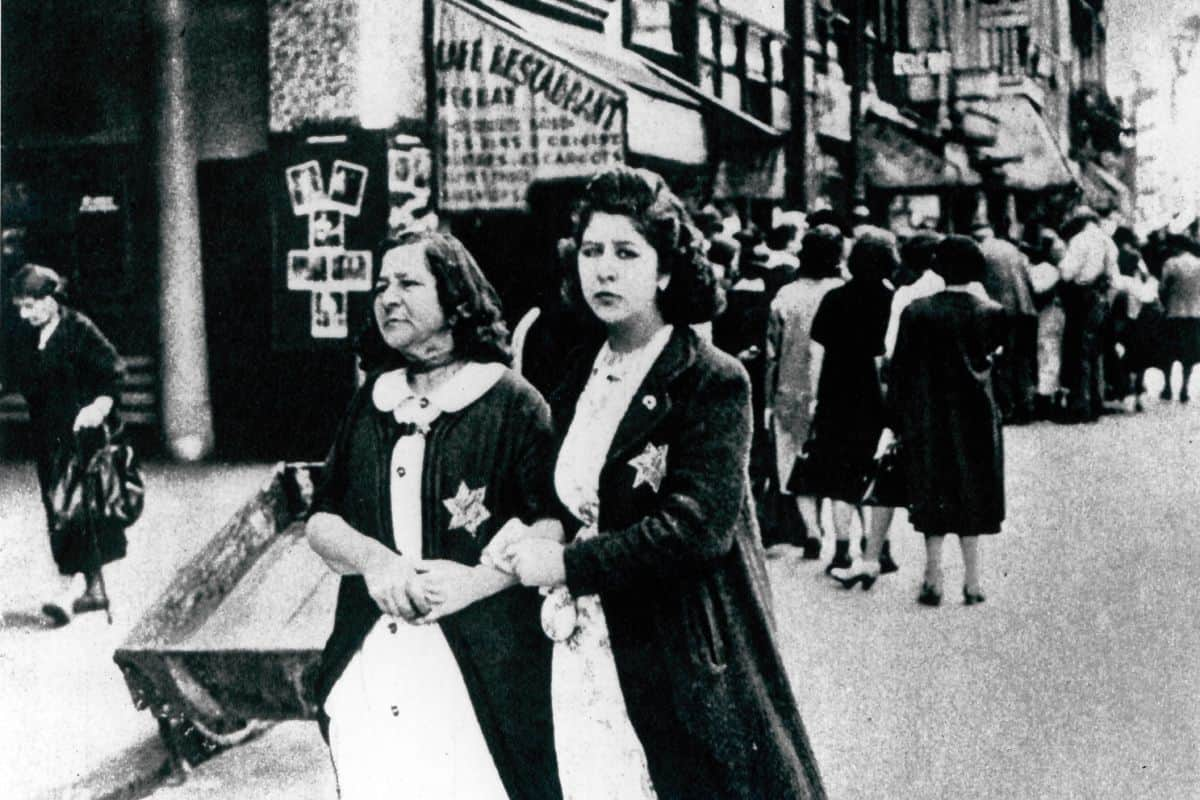 "Nazi occupied countries complied with, and in some cases willingly implemented, Nazi policies and laws. Here two women wear yellow ""Jude"" badges in Paris, France."