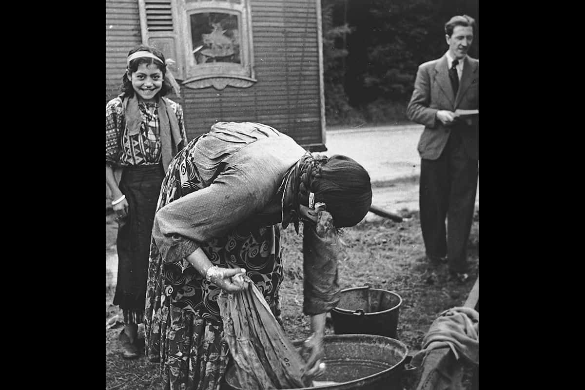 A Roma woman washing clothing in a tub in the 1930s, as a young girl smiles in the background.