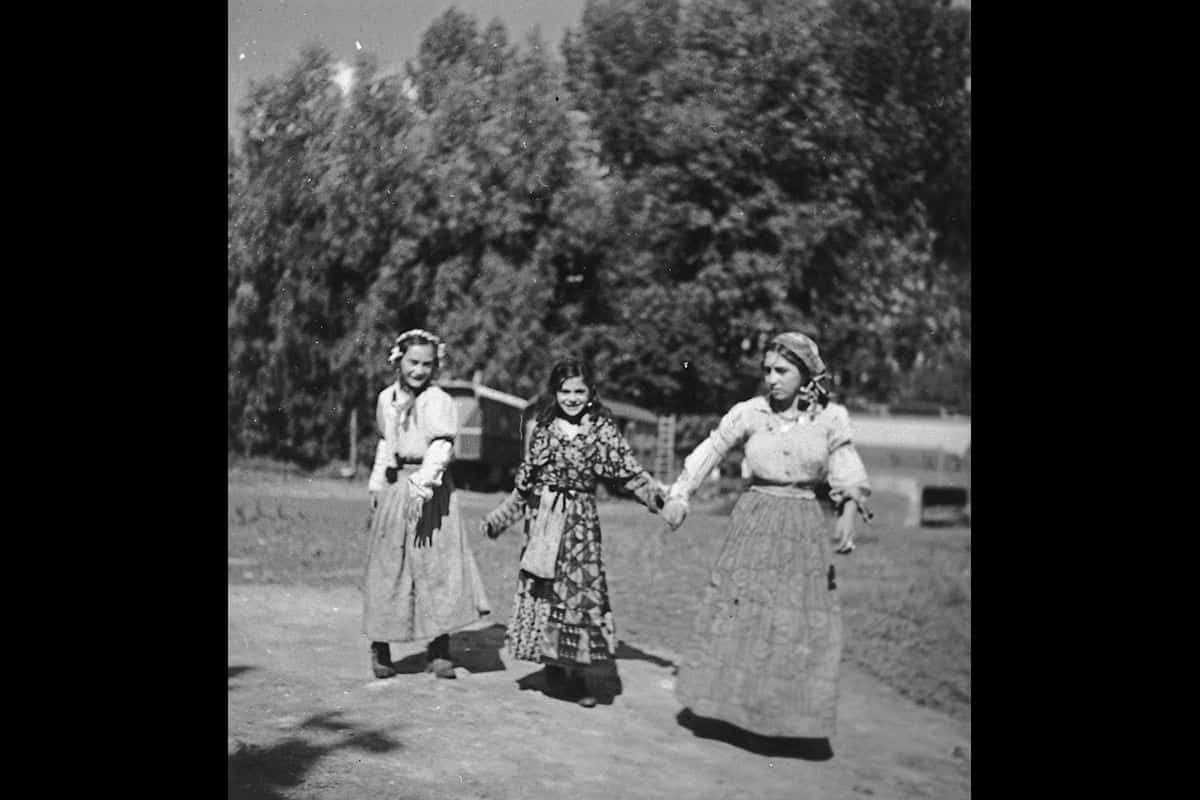 Three young Roma women walk together along a road in 1930s Europe.