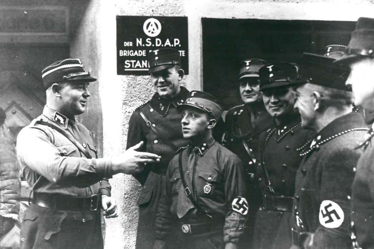 Ernst Röhm was murdered in the event known as the Röhm Putsch, or the Night of Long Knives. As the leader of the SA, Röhm was seen as a threat to Hitler's power. In this photo, Röhm is talking to a group of SA men, who appear to be listening intently.