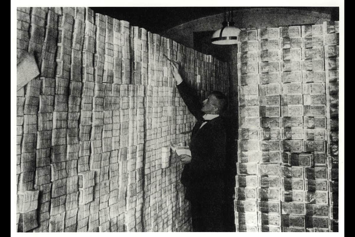 To deal with the economic crisis, the government printed more money. As a result of this, money dropped in value, as more of it was in circulation. This was called hyperinflation. Here, a banker counts stacks of money.