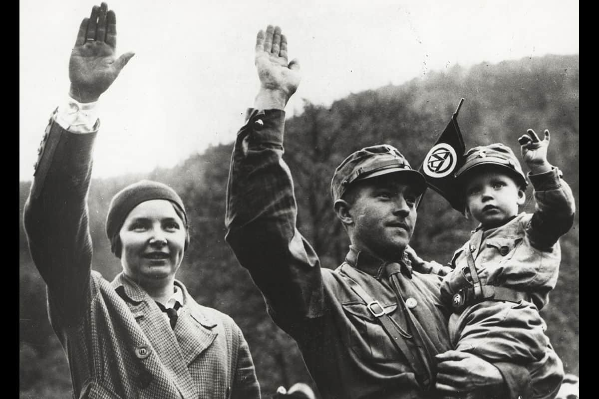 A SA member and his son performing a 'Heil Hitler' salute. Both are wearing the traditional brown SA uniform.