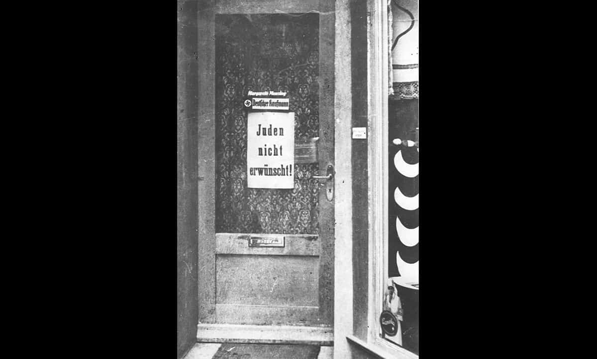 The poster on the door in this photograph reads 'Jews not wanted'. This type of antisemitic signage was visible all over Germany following the Nazis rise to power. It aimed to exclude Jews from every day life. This photograph is taken from The Wiener Holocaust Library's Motorcycle Album, a collection of photographs taken on a journey from the Dutch border to Berlin in 1935.