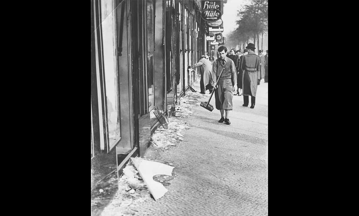 A young man sweeps glass off the streets following the devastation of Kristallnacht.