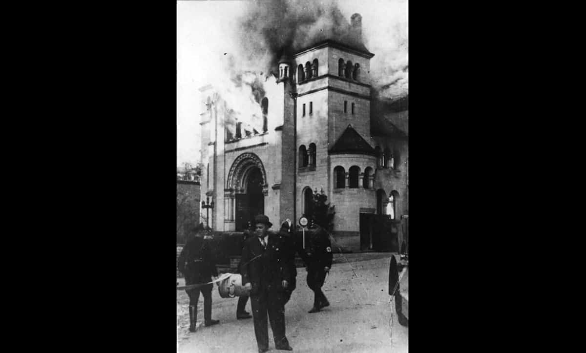 Fire fighters and SS men stand outside the burning synagogue of Baden-Baden during Kristallnacht.