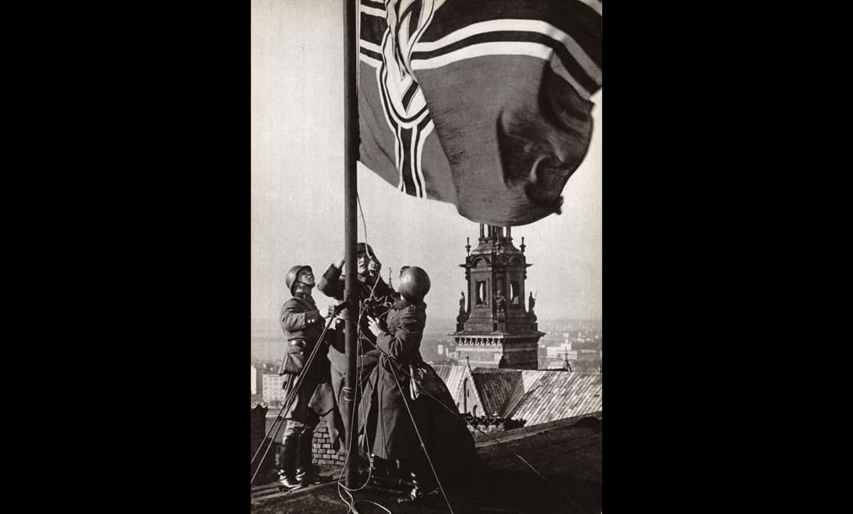 Following the invasion and occupation of Poland, German soldiers hoist the Nazi Flag over Krakow castle in 1939.