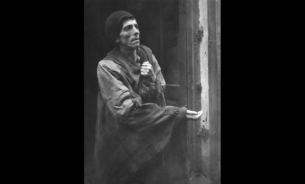 The Warsaw Ghetto was the largest ghetto in Nazi occupied Europe. Conditions within the ghetto became increasingly desperate over the course of the war, with widespread starvation. This photograph shows a man begging for food in the street.