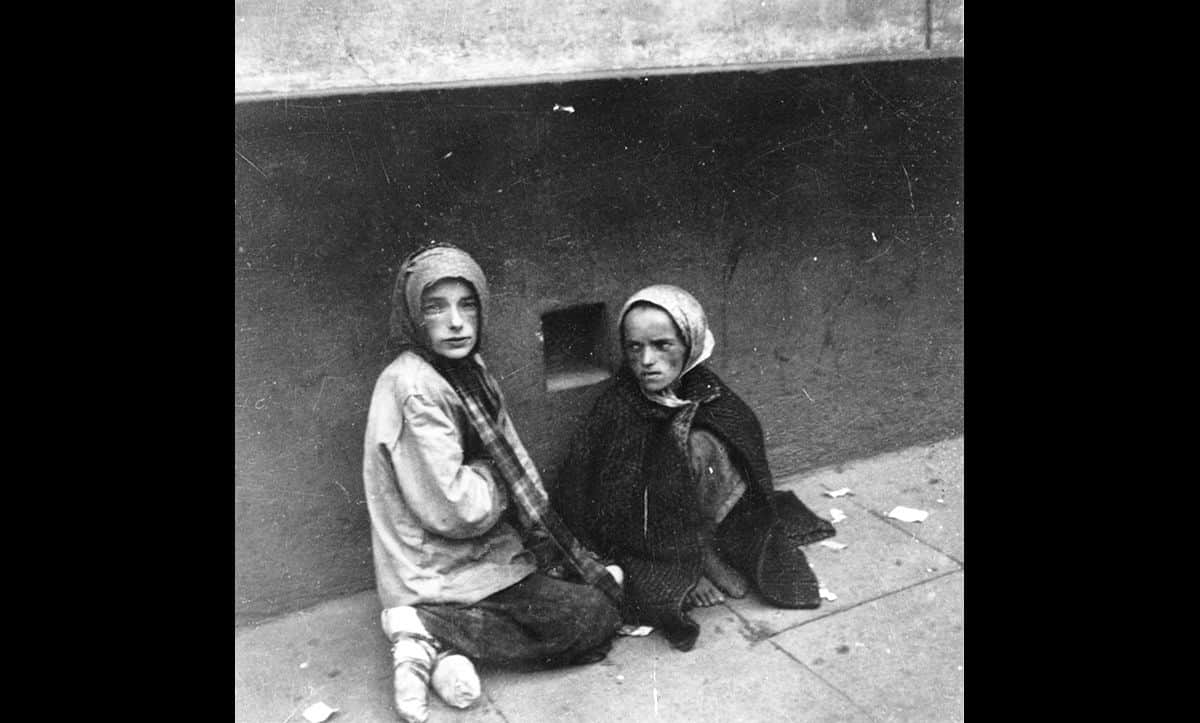 Children suffered harsh circumstances in the Warsaw Ghetto. Here, two children are pictured huddling on the pavement. 