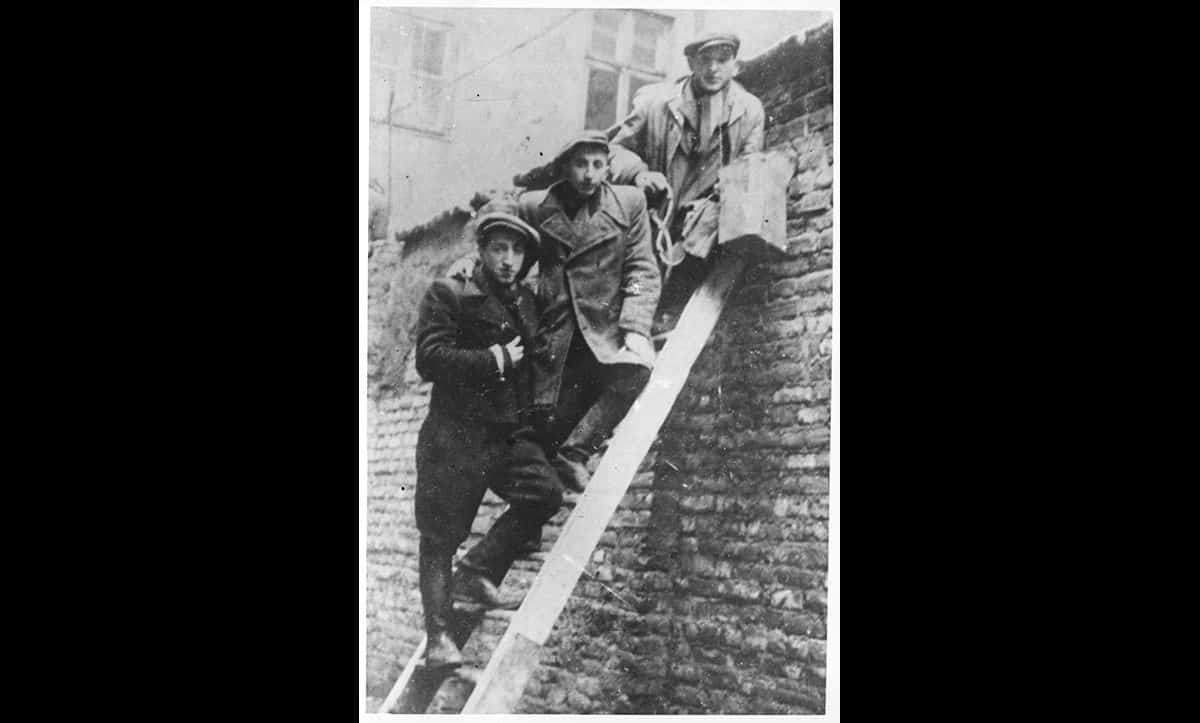 Due to the scarcity of food, smuggling became common. To get food into the ghetto smugglers would scale the walls using ladders, use connecting buildings, the sewers, or workers who regularly entered and left the ghetto.  Photographer unknown.