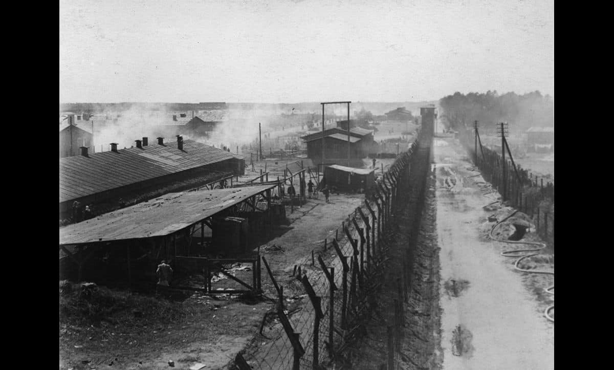 A photograph showing one section of Bergen-Belsen, enclosed by barbed wire.