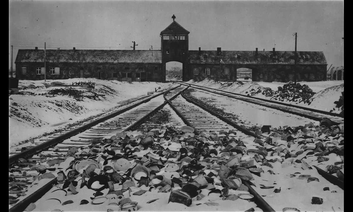Auschwitz was established by the Nazis in March 1942 near the town of Oświęcim in southern Poland. In total, approximately one million people were murdered there during the Holocaust.  This photograph was taken shortly after Auschwitz was liberated in 1945. At the front of the photograph, pots and pans used by the prisoners in the camp are strewn across the ground.