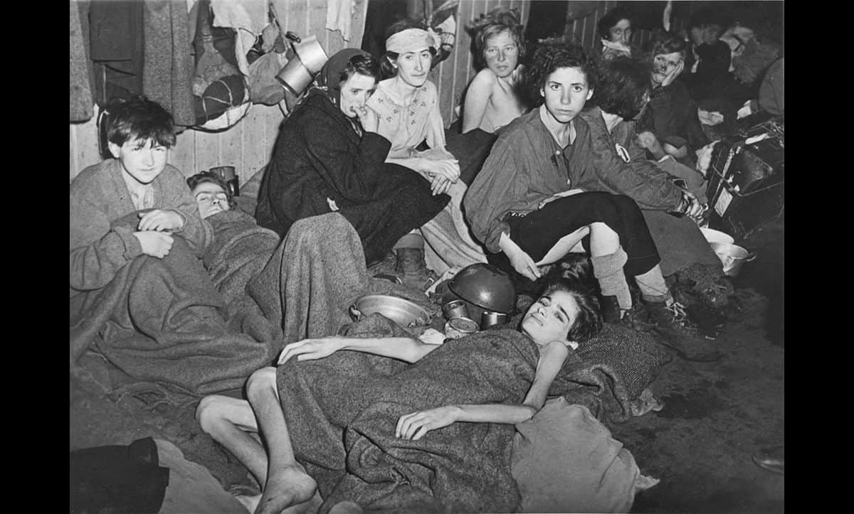 After the British liberated Bergen-Belsen on 15 April 1945, unsanitary conditions did not immediately improve. This photograph shows survivors of the Bergen-Belsen concentration camp, in the aftermath of the liberation.