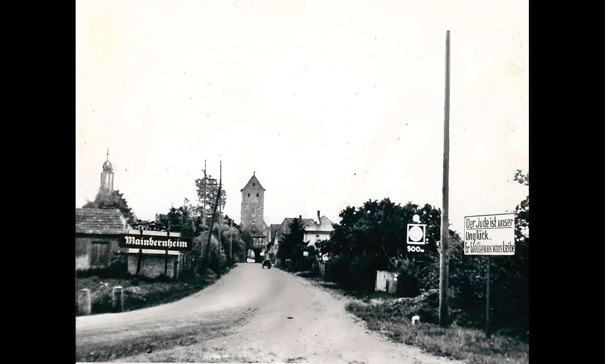 A photograph showing an antisemitic street sign in Mainbernheim, central Germany, taken in September 1935. The sign reads 'The Jew is our misfortune. He shall stay away from us'. This photograph is taken from The Wiener Holocaust Library's Motorcycle Album, a collection of photographs taken on a journey from the Dutch border to Berlin in 1935.
