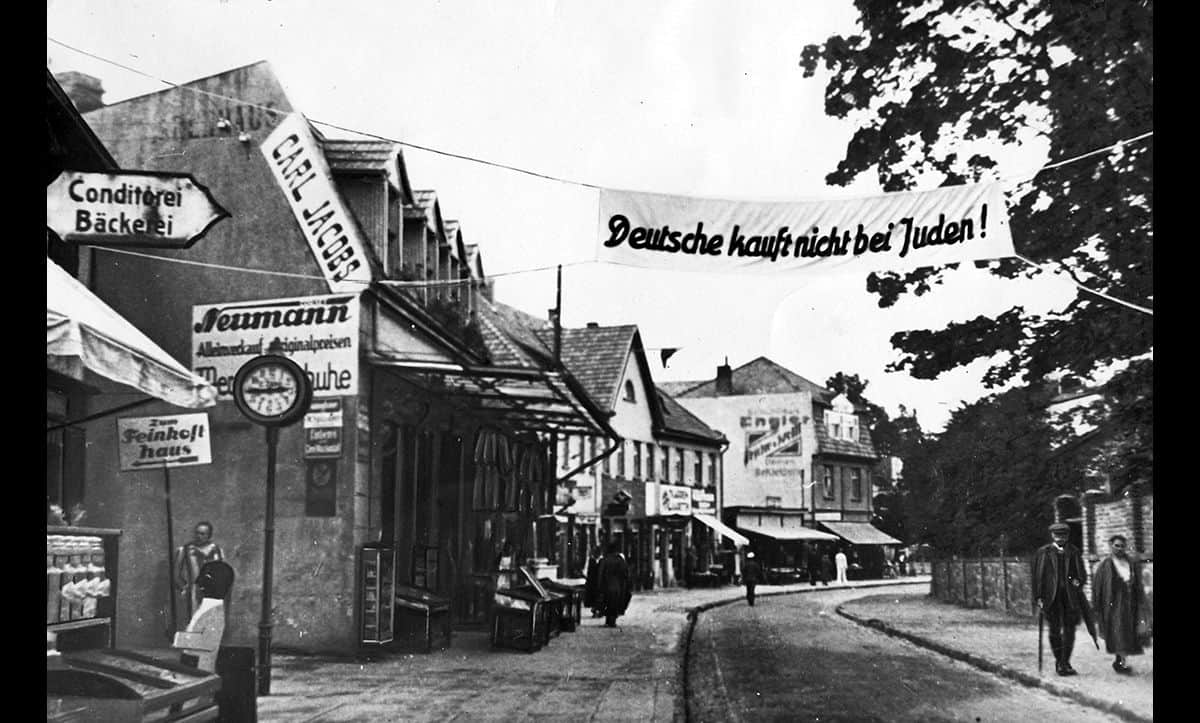 Antisemitism was one of the most fundamental causes of the Holocaust. The banner in this picture reads 'Germany does not buy from Jews'. This photograph is taken from The Wiener Holocaust Library's Motorcycle Album, a collection of photographs taken on a journey from the Dutch border to Berlin in 1935