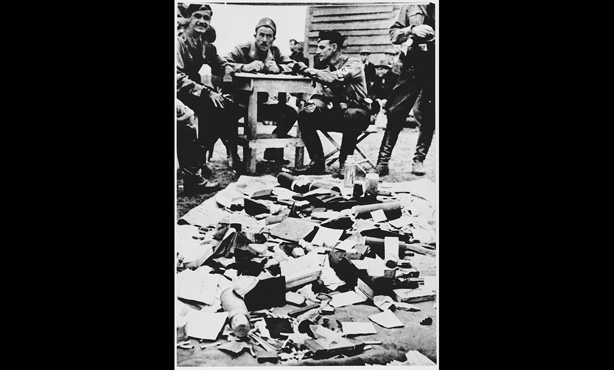 Ustaša personnel at the Jasenovac concentration camp in Croatia sit next to a pile of confiscated property looted from those imprisoned in the camp.
