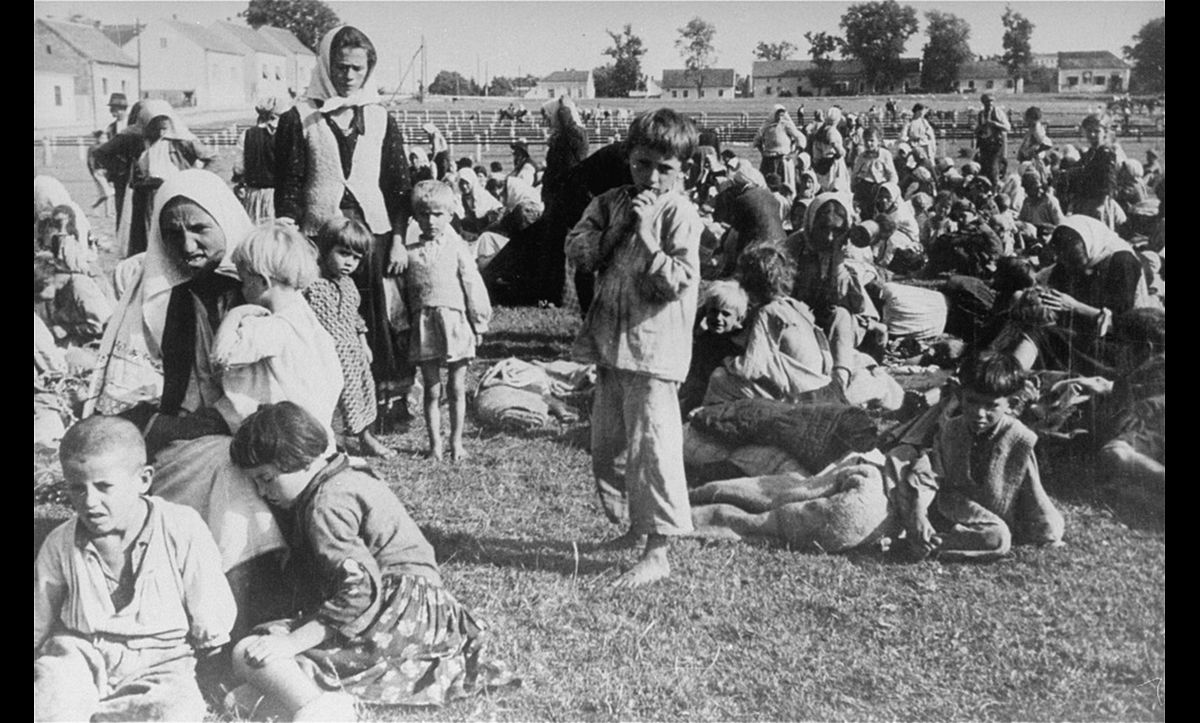 During the war, over 350,000 Serbs were murdered in Croatia by Croatian authorities and organisations. Here, Serbian women and children from the Kozara region sit outside at the Daruvar concentration camp.