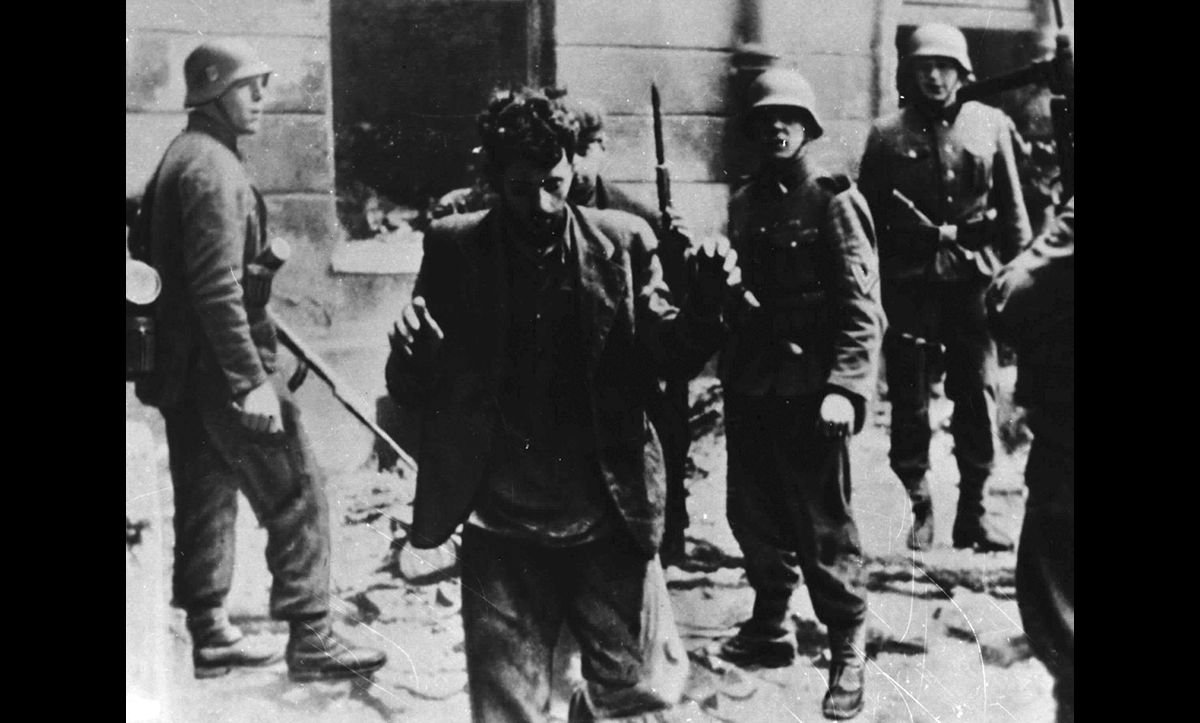 A photograph showing a man being forcibly removed from a bunker in May 1943 following the Warsaw Ghetto Uprising. Following his removal, it is likely that this man was deported to Treblinka and exterminated. This photograph is taken from the Stroop Report, a report written by SS Commander General Jürgen Stroop detailing the events of the Uprising.