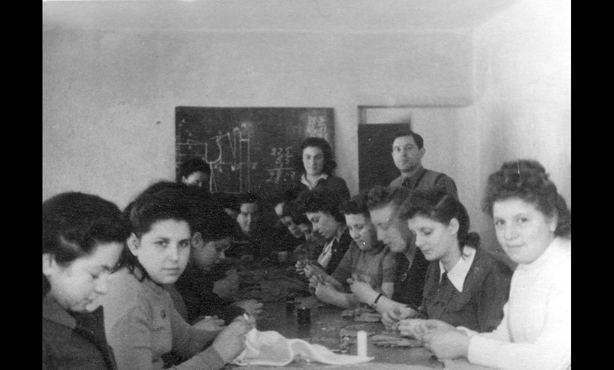 A range of cultural and educational activities were organised across the many DP camps to help DPs acquire new skills and socialise. This photograph shows a inhabitants of Föhrenwald DP camp receiving a class in dressmaking in 1946.