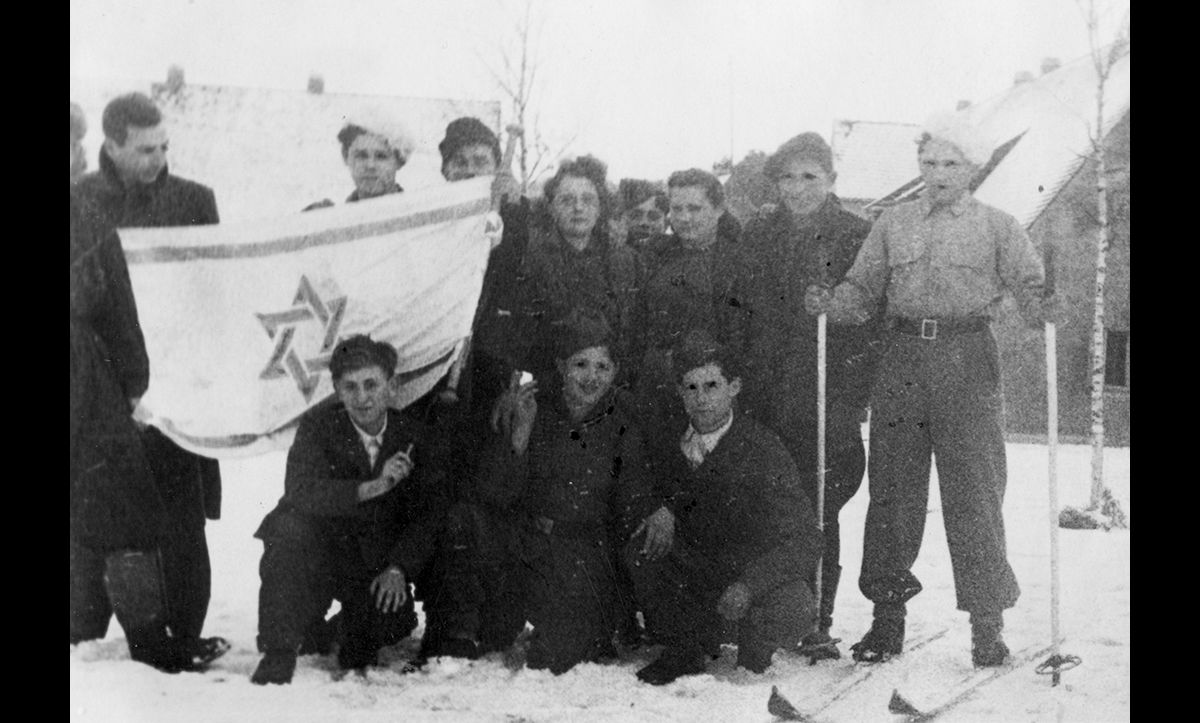 Zionism was widely supported across all DP camps. Here, a group of members of the Kibbutz (a group which taught farming skills and Hebrew to those planning to immigrate to Palestine so that they could form collective farms) at Föhrenwald DP camp in Bavaria are photographed with the Israeli flag in 1946.