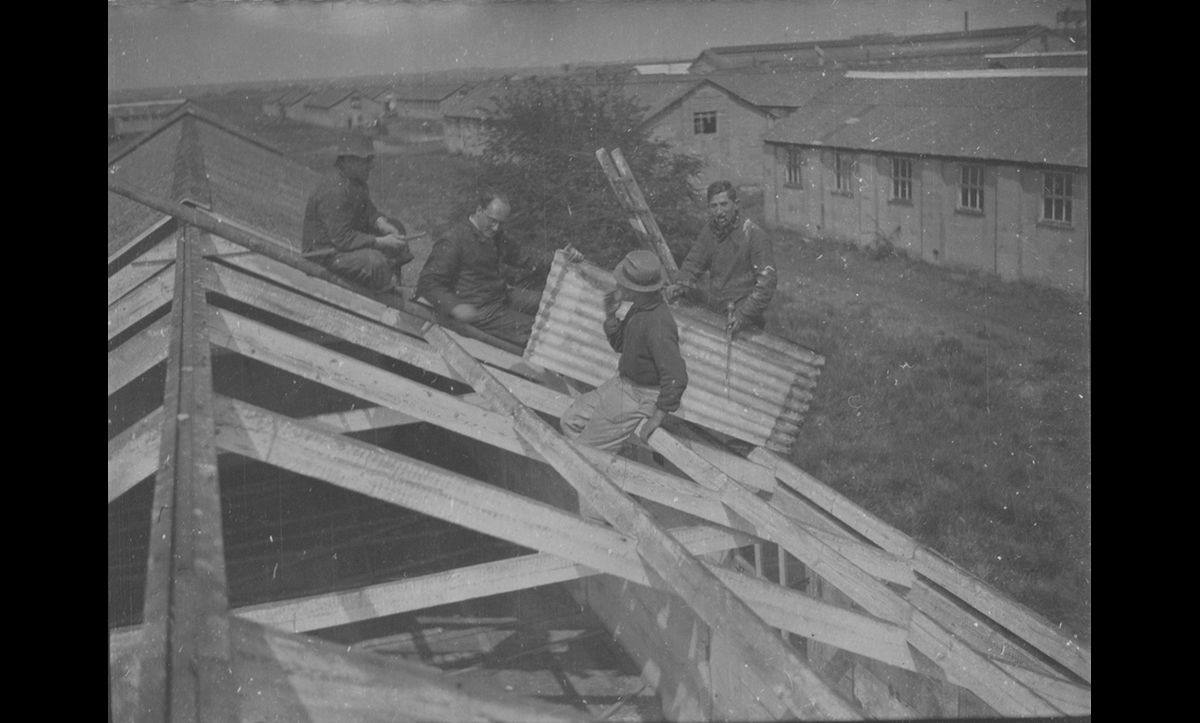 Men from the camp working to renovate some of the old huts.