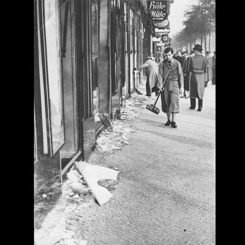 A young boy sweeping up broken glass from a Jewish shop window after Kristallnacht, an anti-Jewish pogrom led by the Nazis in November 1938. Businesses were destroyed, synagogues were set on fire, and over 25,000 Jews were arrested and sent to concentration camps, such as Buchenwald and Dachau.
