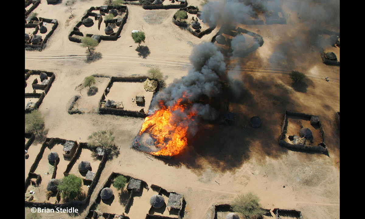 Brian Steidle is a former marine who became a patrol leader in Sudan for the Jount Military Mission monitoring the ceasefire between North and South Sudan. During his time in Sudan, he took photographs which evidence the devastation in the country. This photograph shows the burning of Um Ziefa, a village in Darfur, Sudan, on 12 December 2004.